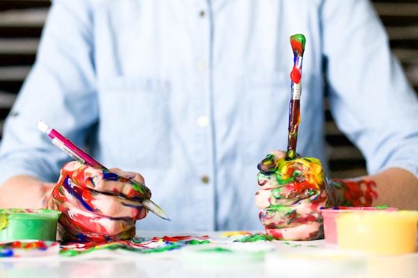 Mann mit farbbeschmierten Händen hält Stift in der Hand